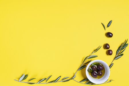 Olive oil and olives on a yellow surface with some Olive branches Stock fotó