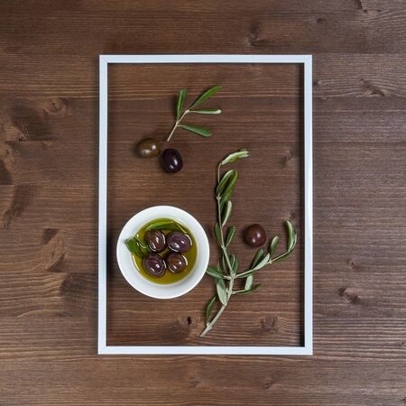 Olive oil with some olives into the frame