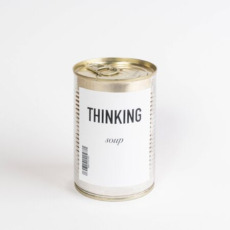 a jar containing soup on a white surface