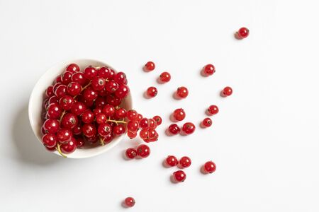 a white bowl with some currant fruits on a white surface