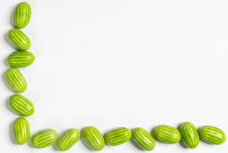 a row of colorful candies with the shape of watermelon on a white surface