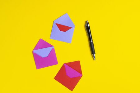 Some greeting cards with  various colors and a pen on a colored surface