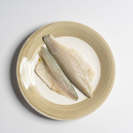 a dish with two fillets of sea bream on a white surface
