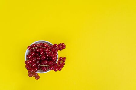 a white bowl with some currant fruits on a yellow surface