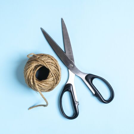 a ball of string and a pair of scissors on a white surface Stock fotó