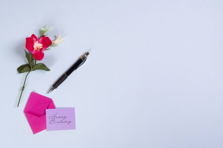 Happy birthday write on a red card with a flower on a blue surface