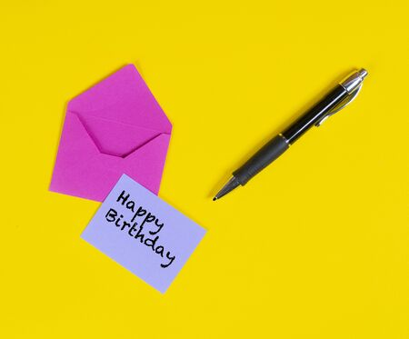 Happy birthday on a red card with a flower on a colored surface