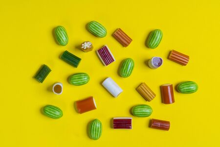 some colorful candies of various shapes on a yellow surface