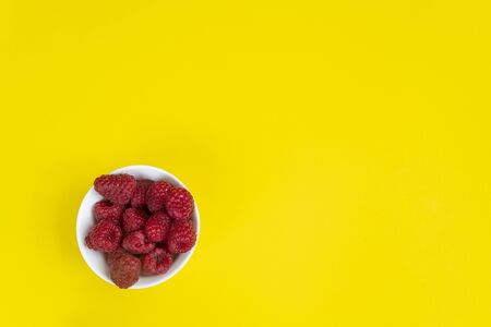 A white bowl with some fruits of  raspberries on a yellow surface Stock fotó
