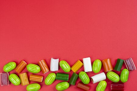 a row of colorful candies of various shapes on a white surface