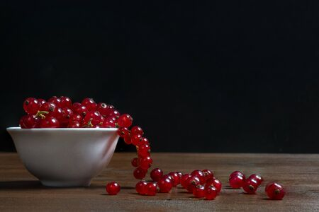a white bowl with some currant fruits on a wooden surface