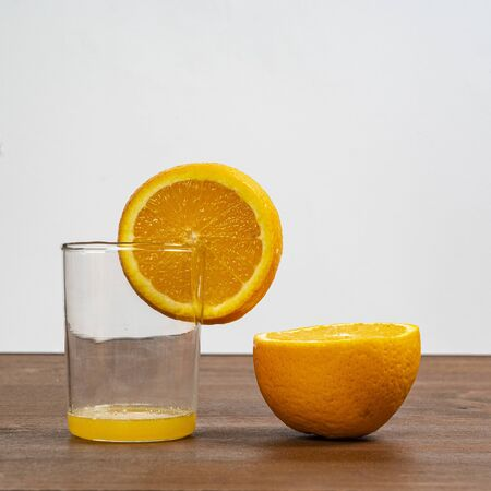 An orange fruit sliced and a glass on a wooden surface