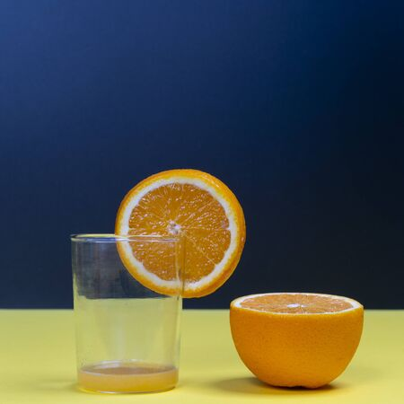 An orange fruit sliced and a glass on a yellow surface 写真素材