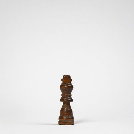 a wooden pawn of the king on a white surface 免版税图像