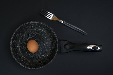 an egg in a pan on a black surface 写真素材