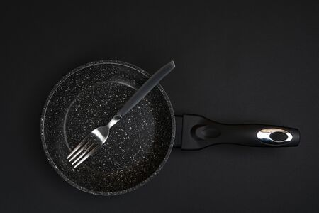 a fork in a pan on a black surface