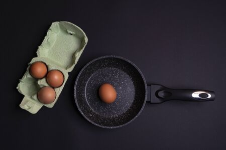 a pan with a man and a cardboard box with some eggs on a black surface 写真素材