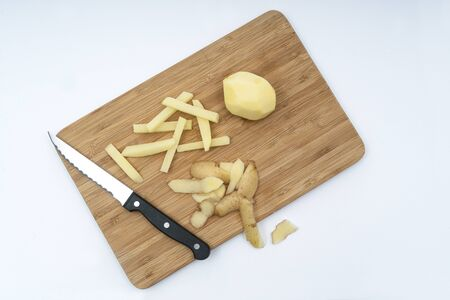 a potato peeled and cut in a stick on a wooden board