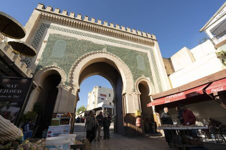 Fez, Morocco. November 9, 2019.  view of Medina vendors in front of the blue gate in the background