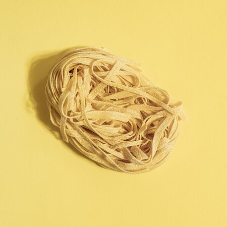 """A """"nest"""" of typical fresh egg pasta on a colored surface"""