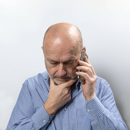 A middle-aged man worried while talking on a cell phone 版權商用圖片
