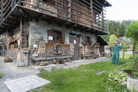 Sauris di Sotto, Italy. May 21, 2020. A typical alpine wooden house with artistic wooden decorations in the Sauris di Sotto village, Italy
