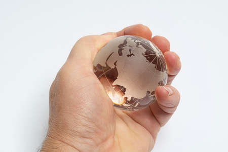 A male hand holds glass earth globe in the hand