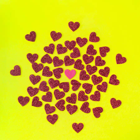 an explosion of small hearts coming out from a white paper bag onto a yellow surface