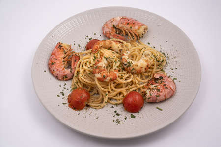 a plate with spaghetti and prawns