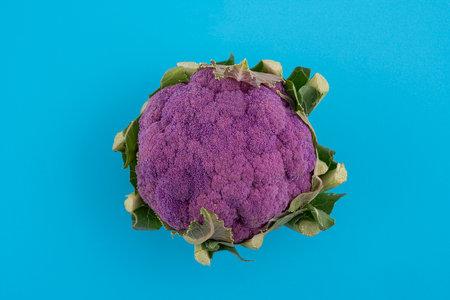 a violet cauliflower in a bag on a blue surface Standard-Bild - 161068620