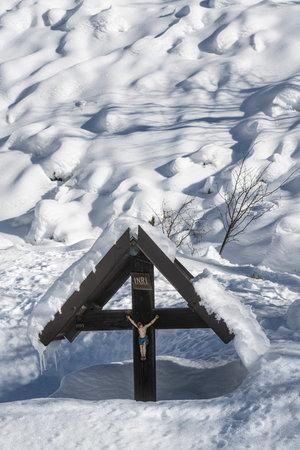a snow covered crucifix in winter Standard-Bild