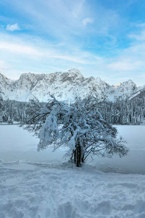 the panorama of the lake of Fusine, Tarvisio, frozen in winter Standard-Bild - 161068646