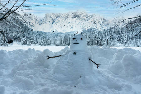 a snowman on the shore of Lake Fusine, Tarvisio, frozen in winter Standard-Bild - 161068648
