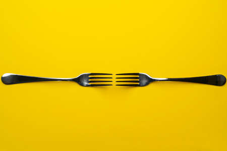 two forks with some types of colored pasta on a yellow surface Standard-Bild - 164074964