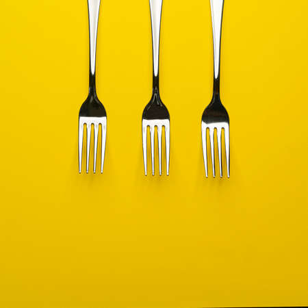 two forks with some types of colored pasta on a yellow surface