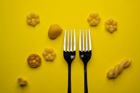 two forks with some types of colored pasta on a yellow surface Standard-Bild - 164076313