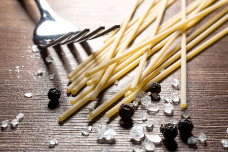 spaghetti, a fork, salt and pepper on an old wooden table Standard-Bild