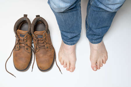 a pair of shoes and a man with bare feet Standard-Bild - 162573452