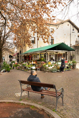 Udine, Italy. February 2 2021. a man sitting on a bench in the winter season in a square in the historic center of Udine Standard-Bild - 163757250