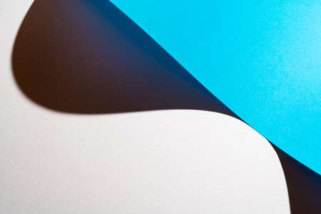the shadow formed by a sheet of light blue paper folded on the white surface Standard-Bild - 163335577