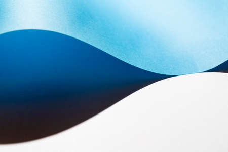 the shadow formed by a sheet of light blue paper folded on the white surface Standard-Bild - 163335403