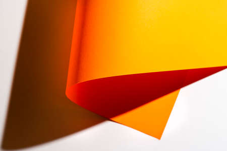 the shadow formed by a sheet of orange paper rolled onto the white surface Standard-Bild