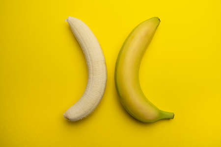 a peeled banana and a whole one in opposite position 스톡 콘텐츠