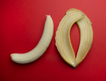 a peel and a peeled banana on a red surface 스톡 콘텐츠