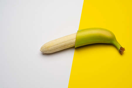 the banana peeled in half on a colored surface