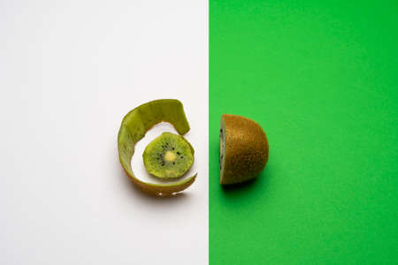 a cut kiwi, half on the green surface and the peel on a white surface
