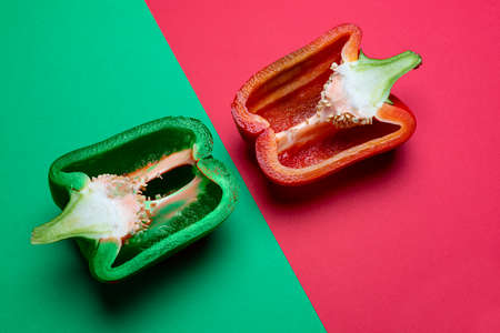 a green and a red pepper cut in half and arranged on a colored surface