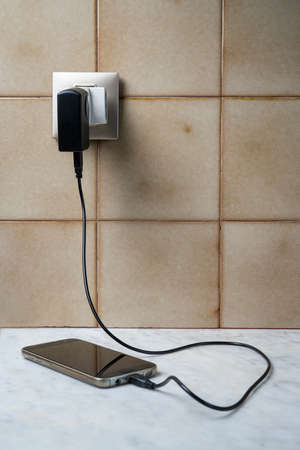 a mobile phone connected to a phug for charging