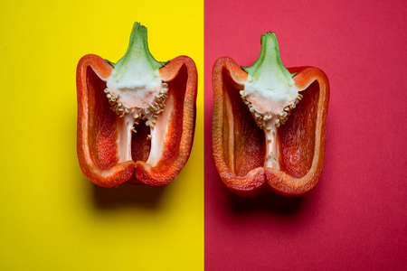 a red pepper cut in half and arranged on a colored surface Standard-Bild