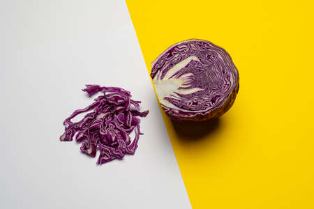 a red cabbage cut in half and placed on a colored surface